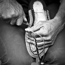 Sohle und Absatz werden Lederschicht für Lederschicht aufgebaut und miteinander verklebt.