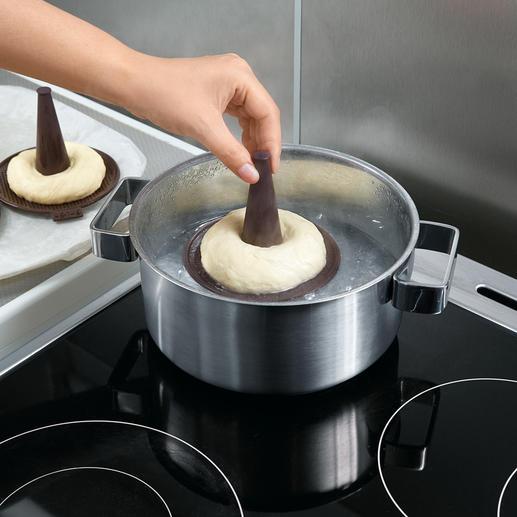 Die Formen mit dem Teig kurz in kochendes Wasser halten